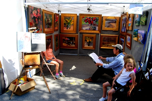 A young subject sits for a fifteen-minute masterpiece at the Prairie Village Art Fair on June 1, 2008. Other young madonnas wait, somewhat listfully in the hot afternoon, for their moment of immortalization.  Photo by Cathy Sherman
