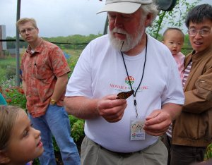 Chip Taylor demonstrates how to hold a Monarch butterfly for tagging.