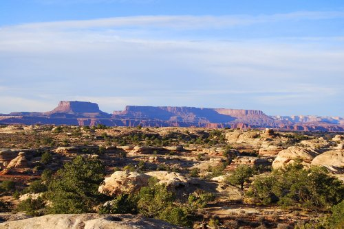 The north section of Canyonlands National Park is the mesa in the center.  This photograph is taken in the Needles district of the park in the Pothole area. Shallow potholes in the rock in the foreground, when filled with rain or melted snow, provide homes for a variety of animals.