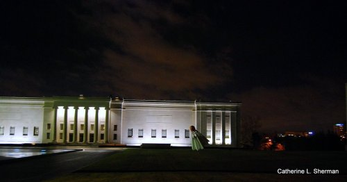 Moonlight iluminates the sky above the Nelson Atkins Museum of Art in Kansas City on Saturday.  One of the Nelson's four giant shuttlecock sculptures, by Claes Oldenburg and Coosje van Bruggen, looks as if it just landed on the front lawn.  There are four shuttlecock sculptures among the many sculptures in the Nelson's Sculpture garden, including a dozen monumental bronzes by Henry Moore and a cast of The Thinker by Auguste Rodin.