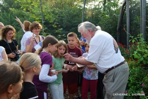 "CHip Taylor shows the students in ""Butterfly School"" where to place the tag on the butterfly's wing."