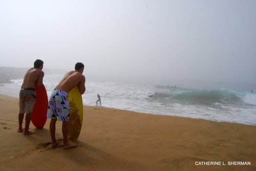 Surfers watch the waves on Newport Beach on a very foggy morning.  The surf was great, but the conditions were probably dangerous. A lifeguard pickup soon showed up and told everyone to get out of the water.  I was standing far back, but a huge wave lashed the beach, and I got splashed and covered with sticky sand.