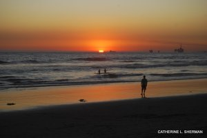 Two surfers head out at sunset on Huntington Beach.  You can see an oil rig in the distance.