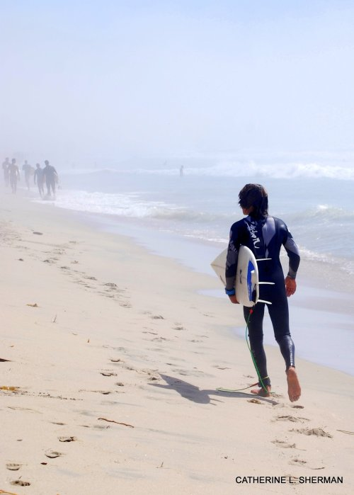 A surfer leaves for the day.  His board is tethered to his ankle so he won't lose it.