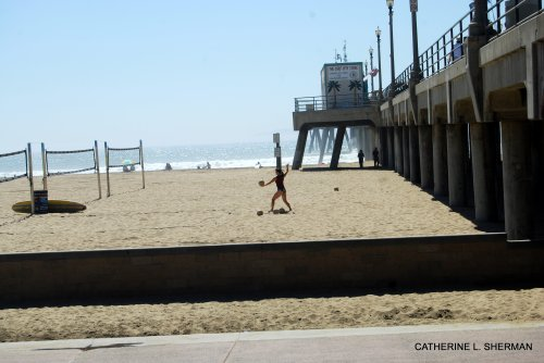 A woman serves a volleyball at the Huntington Beach Pier beach volleyball court.