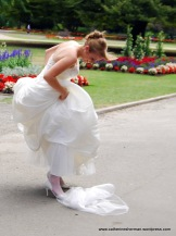 This bride laughs as she stops her wind-blown veil with her foot. She's on her way to a park in Christchurch to get her photograph taken.