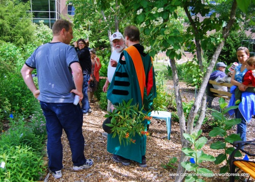 Chip Taylor, founder and director of Monarch Watch, talks with visitors at the 2012 Monarch Watch Spring Open House and Plant Sale at the University of Kansas. Here, a KU faculty member on his way to commencement activities stops to buy some tropical milkweed plants.