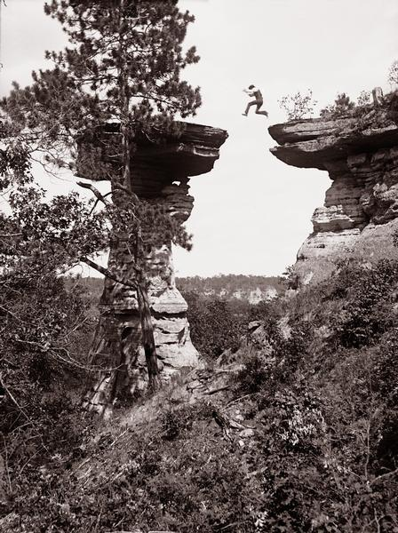 "In 1886, Ashley Bennett jumps from a ledge to Stand Rock in the Wisconsin River Dells in a demonstration of his father Henry Hamilton Bennett's new stop action camera shutter. The photograph is called ""Leaping the Chasm at Stand Rock."""