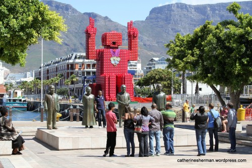 Here's a popular photo stop at the Victoria & Alfred Waterfront in Cape Town, which features statues in Nobel Square of South Africa's four Nobel Peace Prize winners - Albert Luthuli, Desmond Tutu, F. W. de Klerk and Nelson Mandela. I'm not sure what the red sculpture behind is. I think it has something to do with Olympic Medals that South Africa won in 2012.   Does anyone know? I saw photos of the red sculpture under construction from 2010.  In the distance is the iconic Table Mountain.