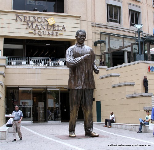 A sculpture of Nelson Mandela dominates the square named after him in Sandton City, an upscale shopping center in Johannesburg, South Africa.
