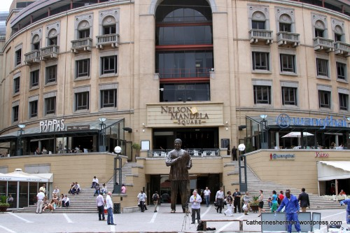 A sculpture of Nelson Mandela is a backdrop to a newscast in Nelson Mandela Square. The square anchors Sandton City, a popular upscale shopping center in Johannesburg, South Africa.
