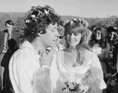 "This October 9, 1969, photograph shows Arlo Guthrie singing ""Amazing Grace"" to his new bride Jackie Hyde, at their wedding ceremony on Guthrie's farm in Washington, Massachusetts. The couple shared a chocolate wedding cake made by Alice Brock, for whom Arlo Guthrie's iconic film ""Alice's Restaurant"" (released in November that year) and song is named. Jackie Guthrie died on October 14, 2012, at the couple's winter home in Florida. They had recently celebrated their 43rd wedding anniversary. (AP Photo/Steve Starr, file)"
