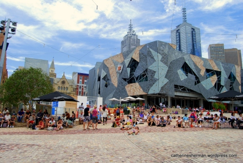 People gather at Federation Square, which is a civic and cultural center in Melbourne, Australia.  About Federation Square.