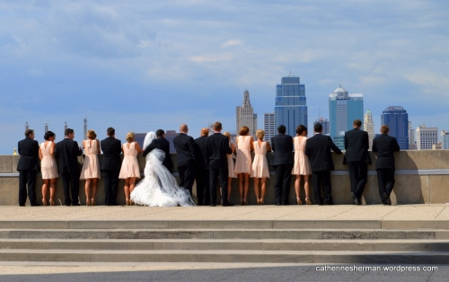 A bride and groom and their attendants pose for a photograph at the overlook at Liberty Memorial in Kansas City, which has a great view of Union Station and downtown Kansas City.