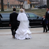 Here's an elegant newlywed pair heading for their limousine after their wintertime wedding ceremony.