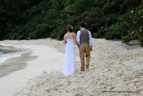 A bride and groom walk on a beach in St. John, Virgin Islands, which is a favorite for destination weddings.
