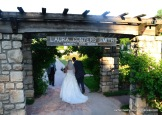 Newlyweds walk under a pergola at the Laura Conyers Smith Municipal Rose Garden in Kansas City, a popular spot for weddings.