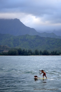 A man and his dog paddleboard in Hanalei Bay on the island of Kaua'i in Hawai'i.