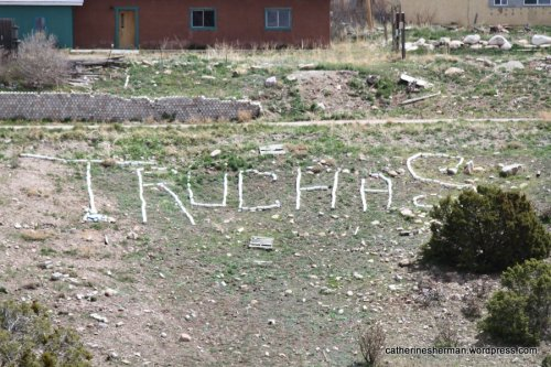 On a hillside, stones spell out the name of the city of Truchas.