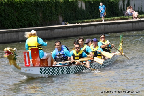Thess dragon boat crew members paddle hard as they reach the finish in the International Dragon Boat Festival on June 14, 2014, on Brush Creek in the Country Club Plaza in Kansas City, Missouri.