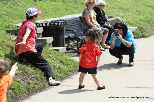 Spectators have fun while waiting for the next dragon boat race to begin on Brush Creek in Kansas City.