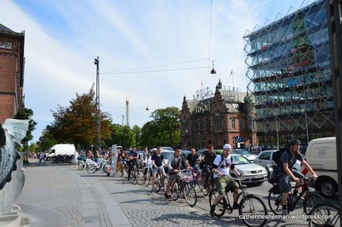 A crowd of bicyclists peddle rapidly at rush hour on H.C. Andersens Boulevard at the Town Hall Square in Copenhagen, Denmark.