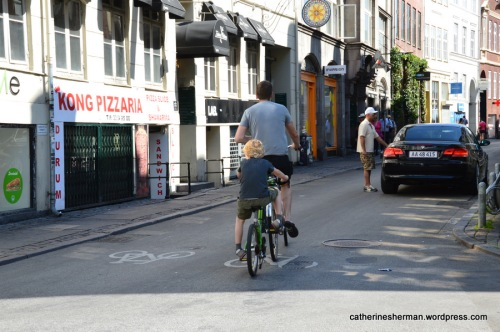 A father and son ride a tandem bicycle in Copenhagen, Denmark.