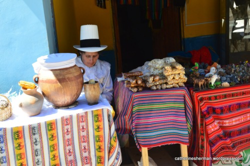 A woman waits in her shop, selling food, woven goods, salt and souvenirs at the market at the salt pans, near Maras, Peru.