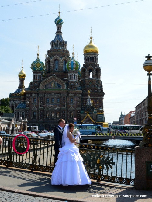 The Church of the Spilled Blood in St. Petersburg, Russia, is a popular backdrop for newlywed photos.  Here a couple stands on a bridge over one of St. Petersburg's many canals with the onion domes of the church behind them. In the red circle, not really visible in this photo, is one lock attached to the bridge rail.  I'm not sure whether this trend hasn't caught on yet in St. Petersburg, or whether previous locks have been removed.