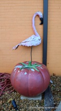 A metal flamingo and a concrete tomato hang out at a Jacksonville, Texas, restaurant.